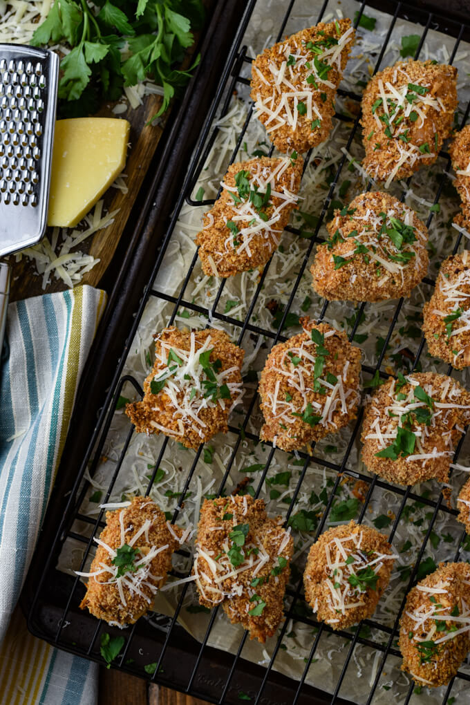 Baked chicken bites sit on a wire rack in a cooking sheet with parchment paper. Grated parmesan and chopped parsley have been sprinkled on them.