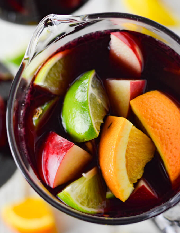 A closeup photo from above of a pitcher of red wine sangria with chunks of fresh apples, oranges, lemons and limes. Two glasses filled with the sangria sit beside the pitcher. Chucks of the fresh fruit are scattered on the board below.