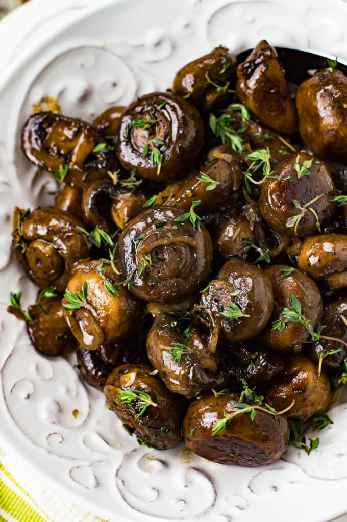 Sauteed marsala mushrooms with thyme sprinkles over the top sit in a white bowl.