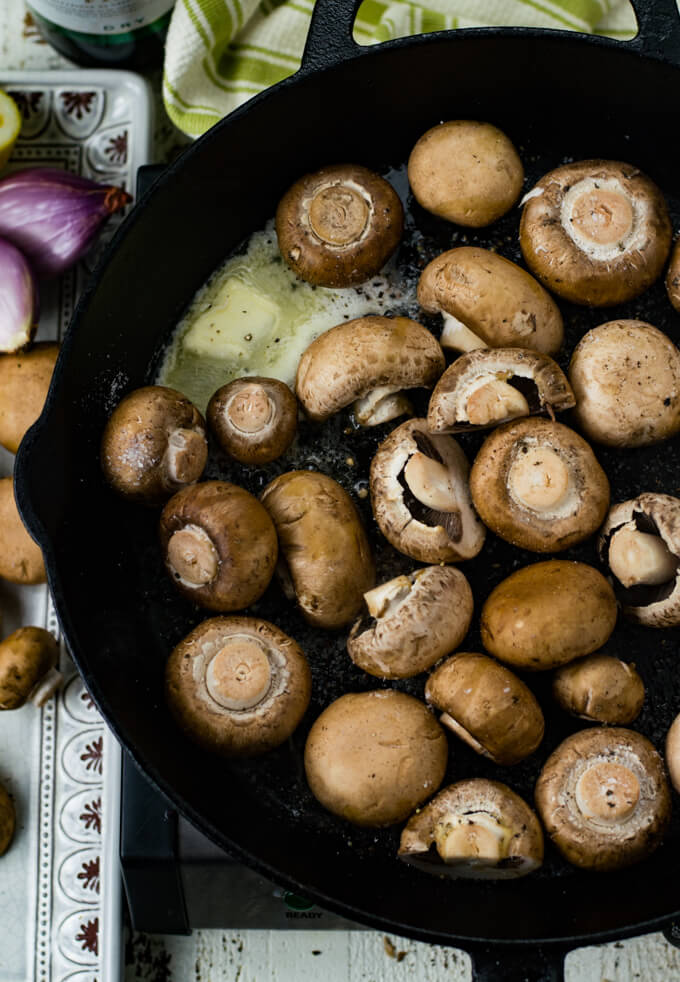 Whole mushrooms are in a cast iron skillet with butter melting.