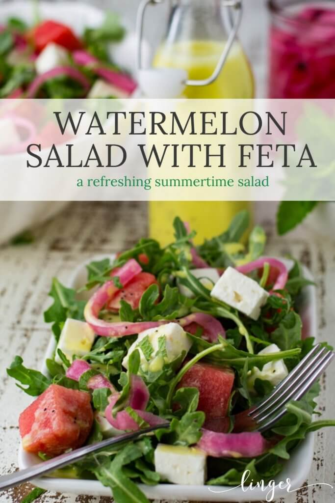 A white plate with watermelon arugula salad. Feta cheese and pickled onion are in the salad as well. It's drizzled with poppyseed dressing. Mint, a bottle of dressing and pickled onions sit next to the bowl.