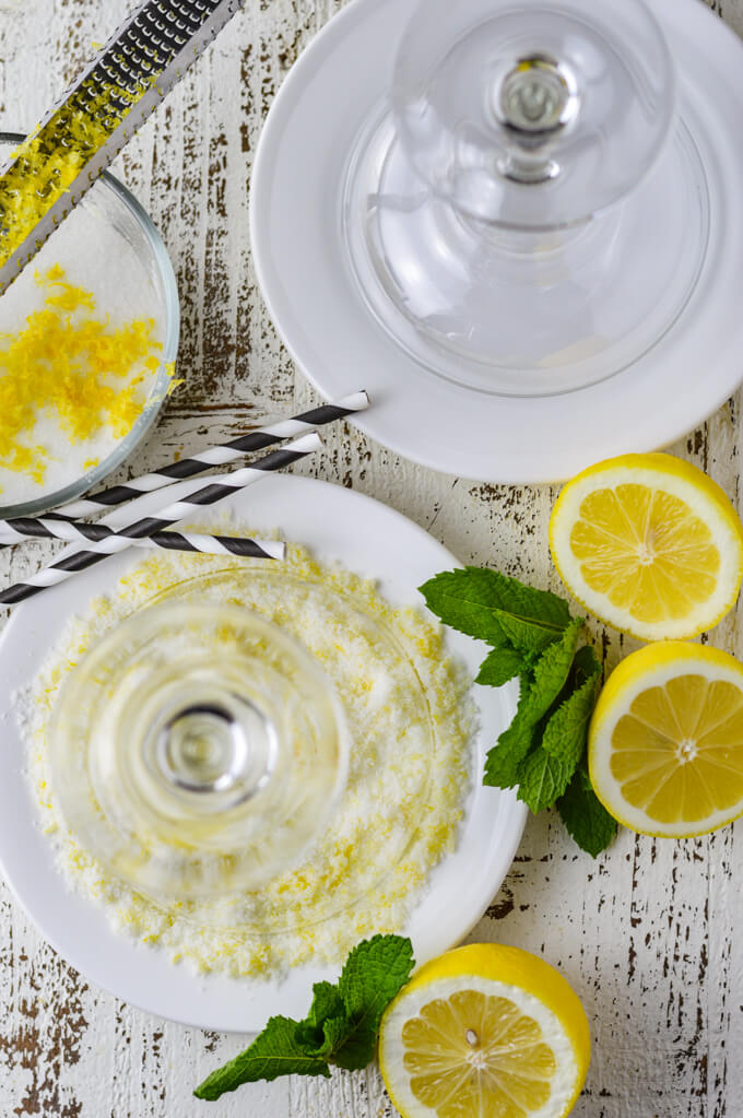 One margarita glass sits upside down on a white saucer with lemon sugar on the saucer. Another white sauce with water and an upside down margarita glass. A bowl of sugar with lemon zest sitting on top. Two lemon halves and fresh mint sit beside them ready to go into a margarita cocktail.