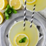An overhead view of a glass of limoncello margarita sitting on a silver tray with black and white napkins. Another margarita glass sits next to it. Both have black and white striped straws sticking up. Lemons and fresh mint sit next to the glasses.