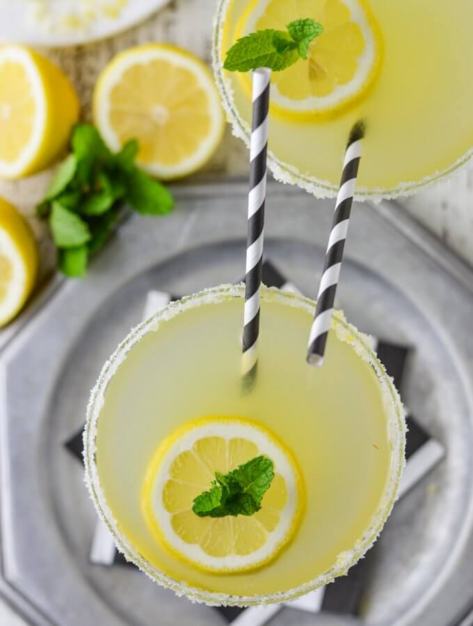 An overhead view of a glass of limoncello margarita cocktail sitting on a silver tray with black and white napkins. Another margarita glass sits next to it. Both have black and white striped straws sticking up. Lemons and fresh mint sit next to the glasses.