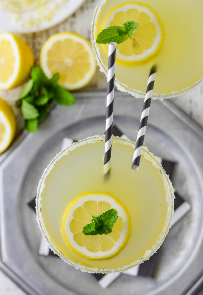 A overhead view of a glass of a limoncello margarita cocktail sitting on a silver tray with black and white napkins. Another margarita glass sits next to it. Both have black and white striped straws sticking up. Lemons and fresh mint sit next to the glasses.