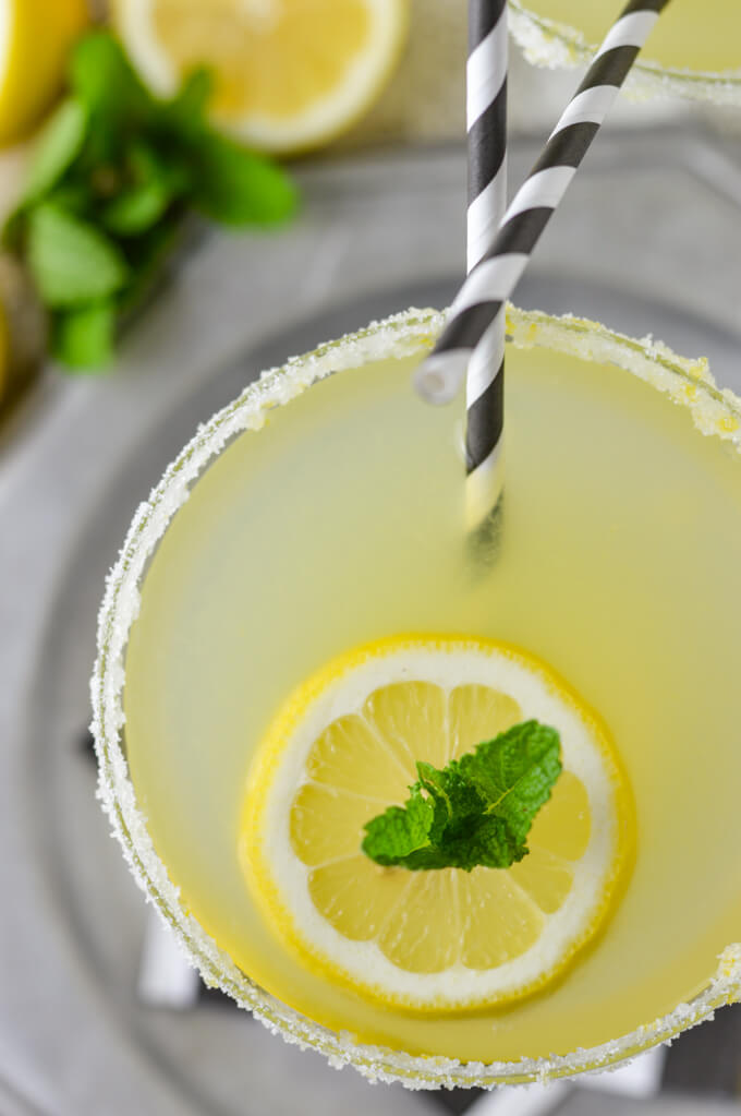 An overhead close-up view of a glass of a limoncello margarita cocktail. A slice of lemon sits on top with a sprig of fresh mint. A black and white striped straw sits in the glass.