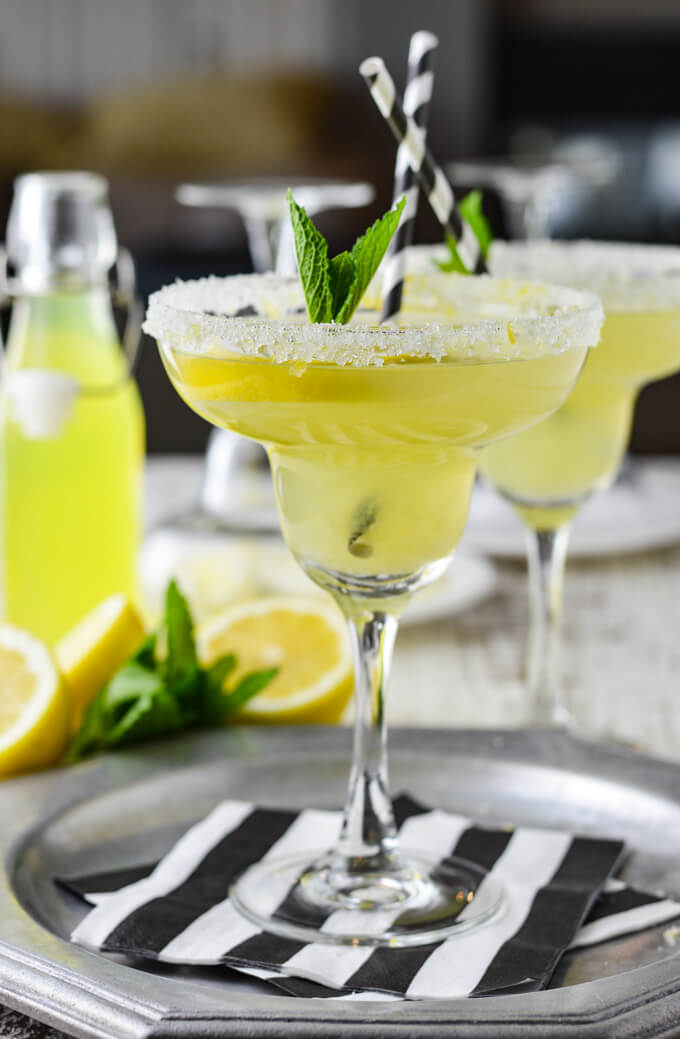 A front view of 2 limoncello margaritas with a sugared rim and a garnish of fresh mint. One glass sits on a silver plate and black and white napkins.