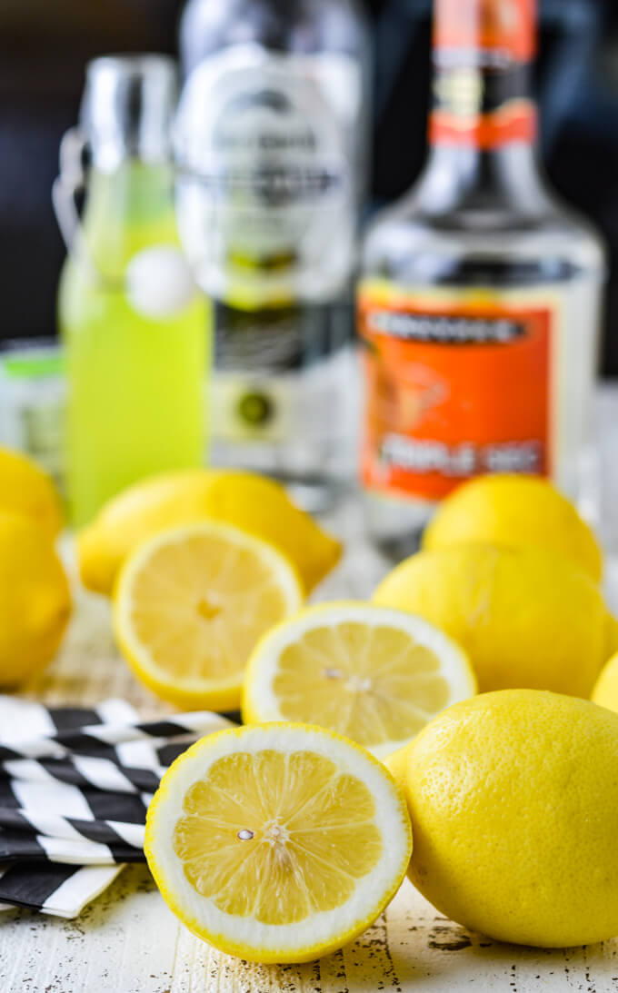 A bunch of whole and half lemons are scattered around with black and white striped napkins near them. Bottles of alcohol for limoncello margaritas are in the background.