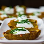 Three loaded potato skins topped with bacon, cheese and sour cream sitting in a row on a stack of white appetizer plates. Blurred potato skins sit in the background.