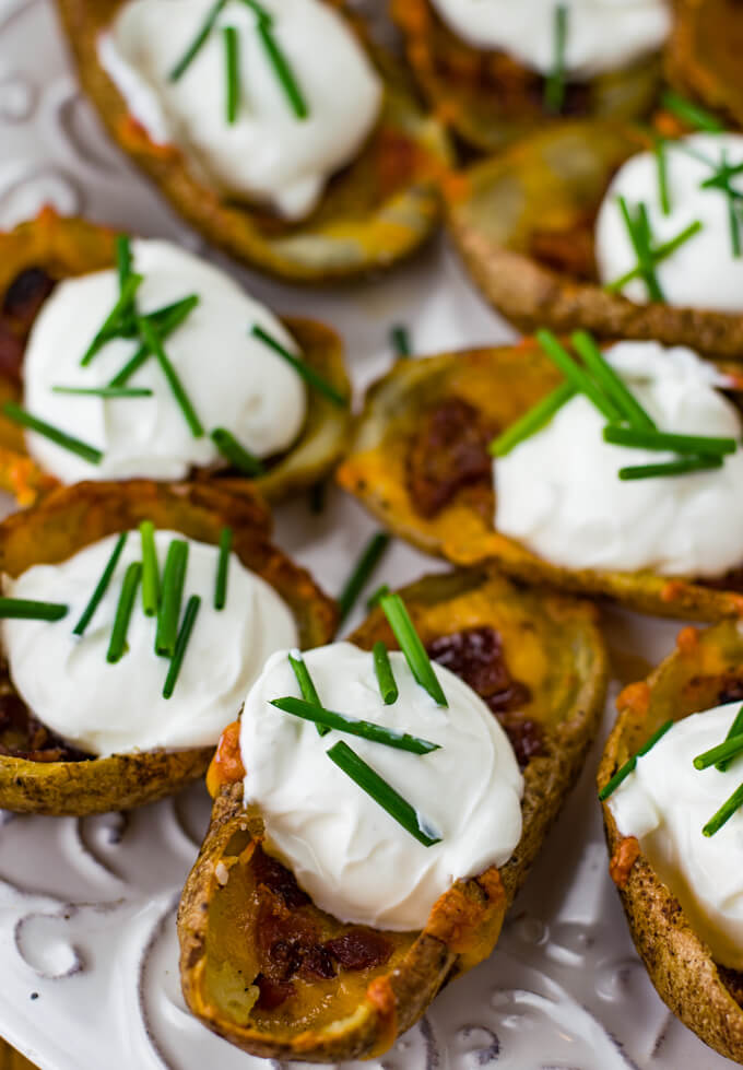 Baked loaded potato skins with cheese, bacon, sour cream and chives sit on a white plate.