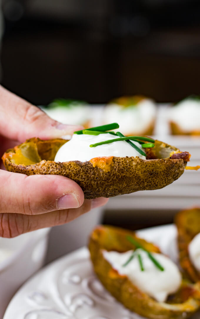 A hand is holding a loaded potato skin topped with cheese, bacon, sour cream and chives. More potato skins are blurred in the background.