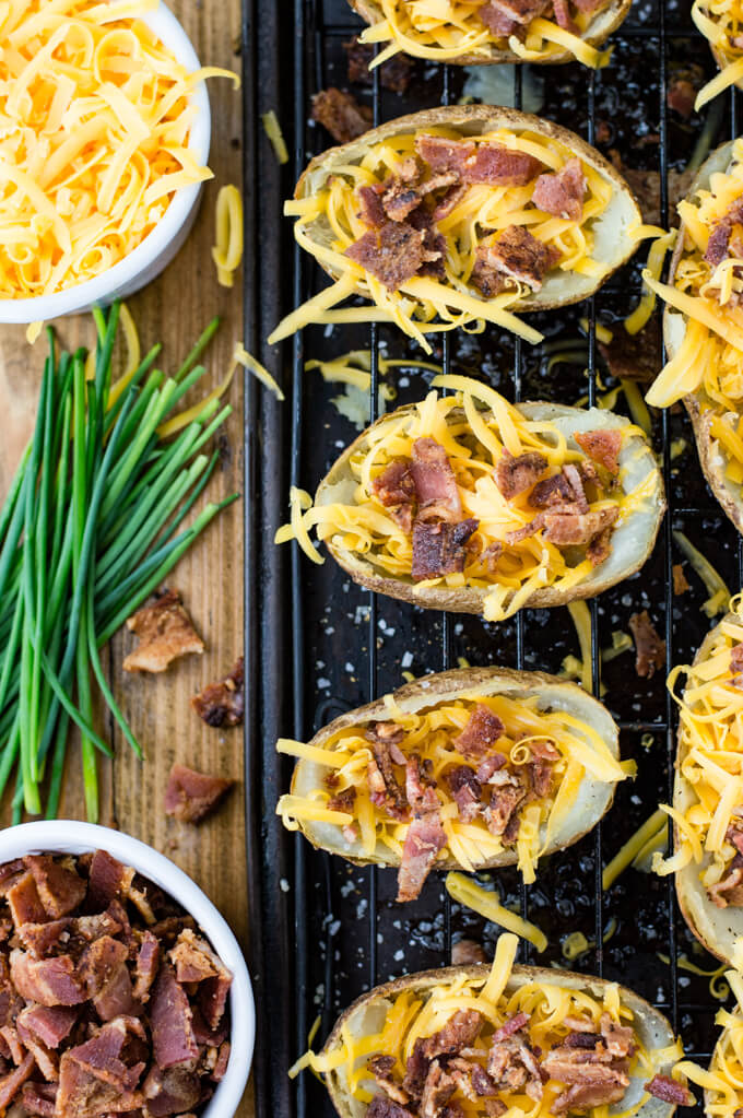 Halved potato skins with shredded cheese and bacon bits sprinkled on them sit on a wire rack on top of a baking sheet. A bowl of cheese and bacon and chives sit next to the skins.