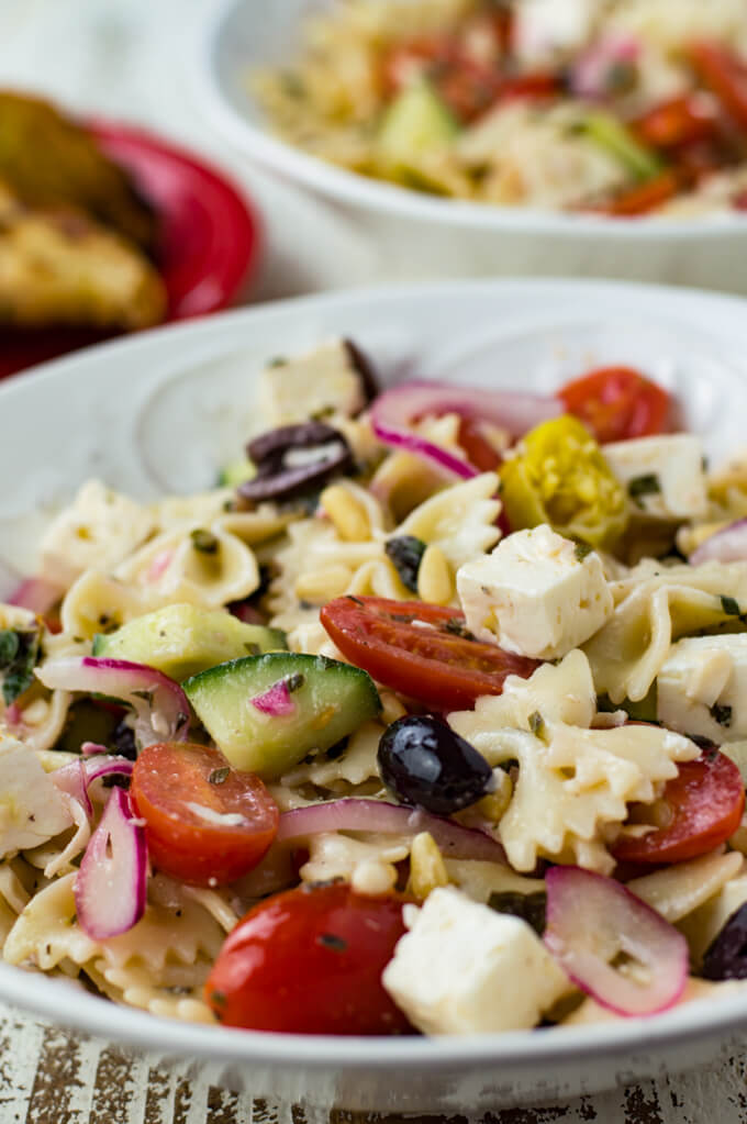 A white bowl of mediterranean pasta salad with a fork and knife beside it. Crusty bread sits in the corner of the photo.