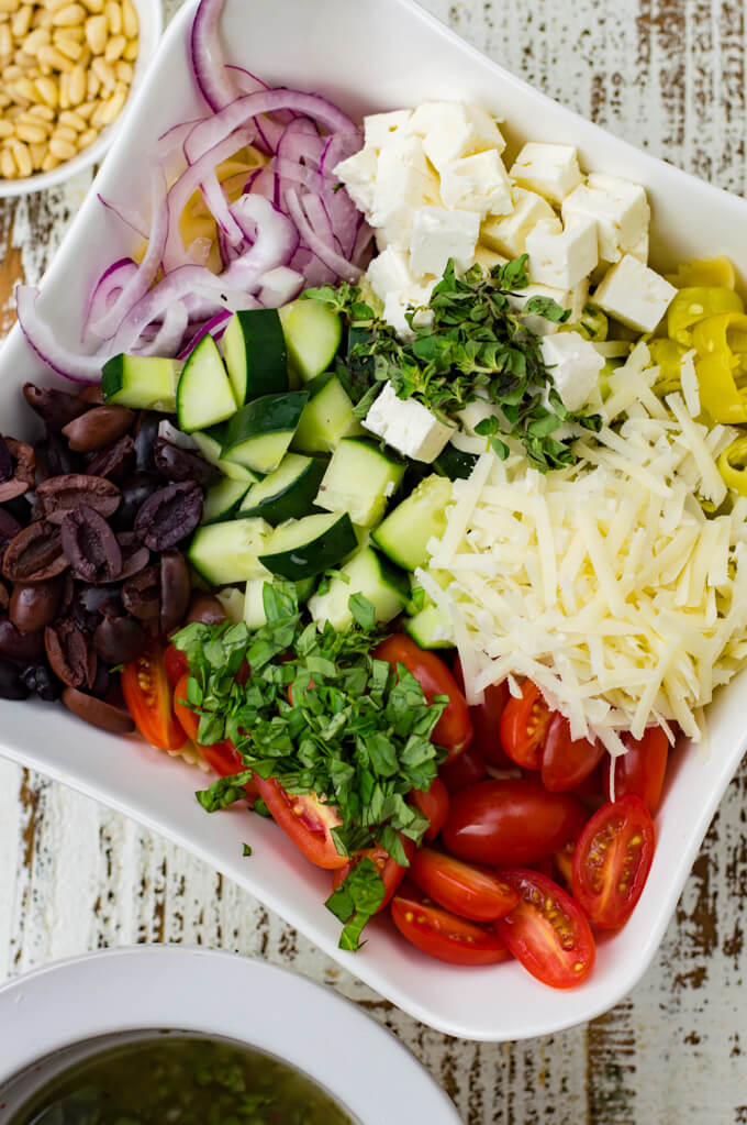 A white serving bowl holds pasta, tomatoes, onions, olives, cucumbers, herbs and feta cheese.