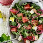 A white serving bowl with watermelon arugula salad. Feta cheese and pickled onion are in the salad as well. It's drizzled with poppyseed dressing. Mint, a bottle of dressing and pickled onions sit next to the bowl.