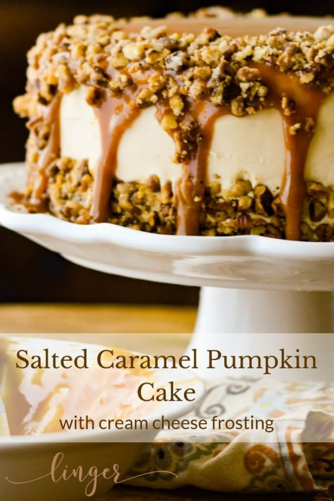 A salted caramel layered pumpkin cake on a white cake stand.