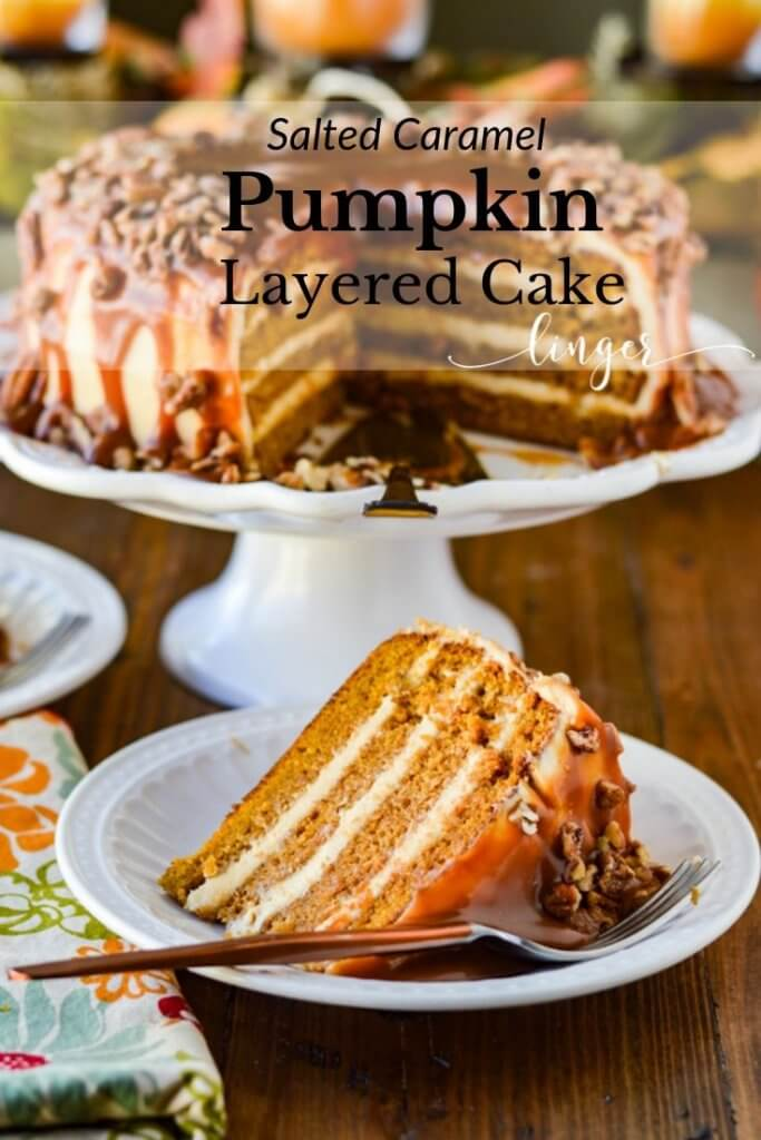 A slice of layered pumpkin cake is served on a white plate with a fork beside it. There's a colorful napkin beside it. The rest of the cake sits in the background on a white cake stand.