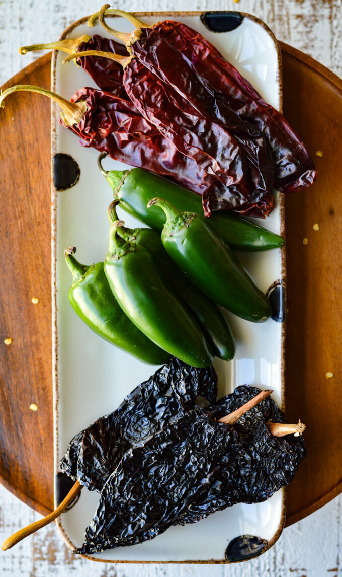 Dried Ancho Chilis, 5 fresh jalapeño chilies, and 5 Dried California Chilies on a black polka dot platter