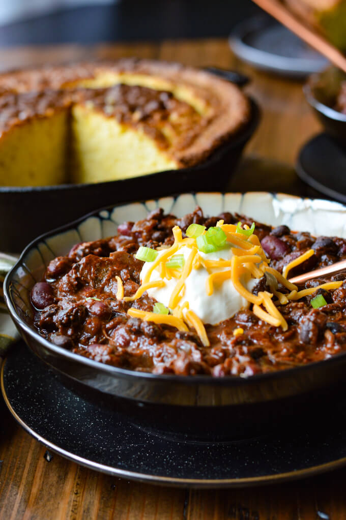 A bowl of Beef Short Rib Chili with cornbread sitting next to it.