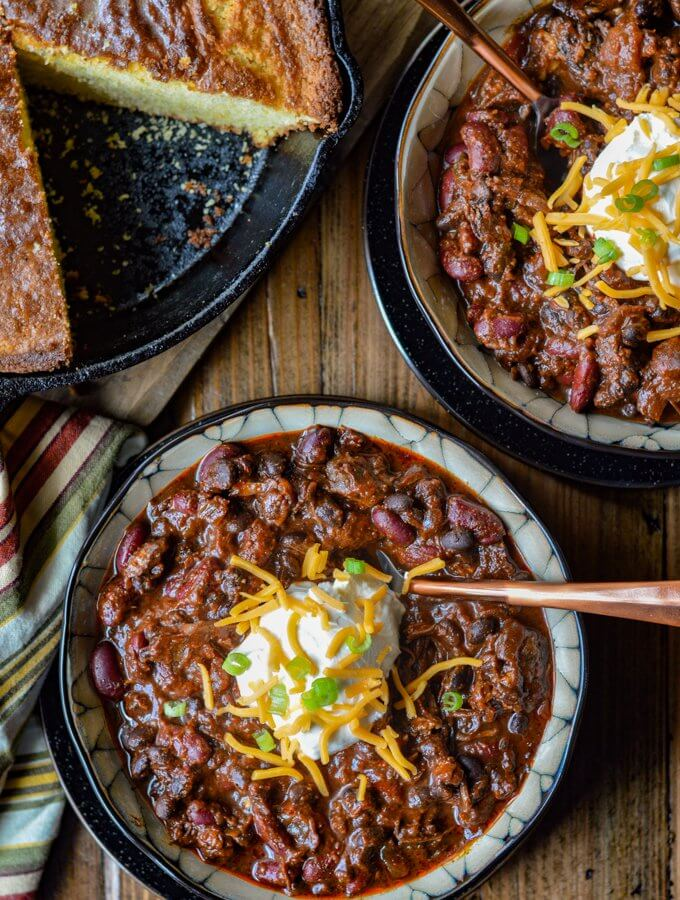 Two bowls of Beef Short Rib Chili with cornbread in a cast iron pan on the side