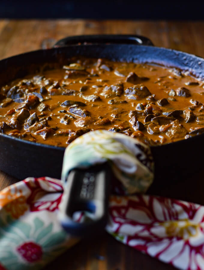 A front view of beef stroganoff in a cast iron skillet with a napkin wrapped around the handle.