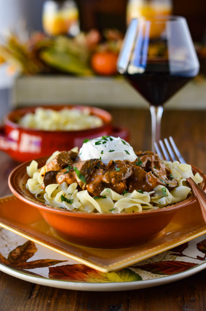 Beef Stroganoff on a bed of buttered egg noodles in fall dinnerware next to a glass of wine. There is a side dish of noodles and striped napkin.