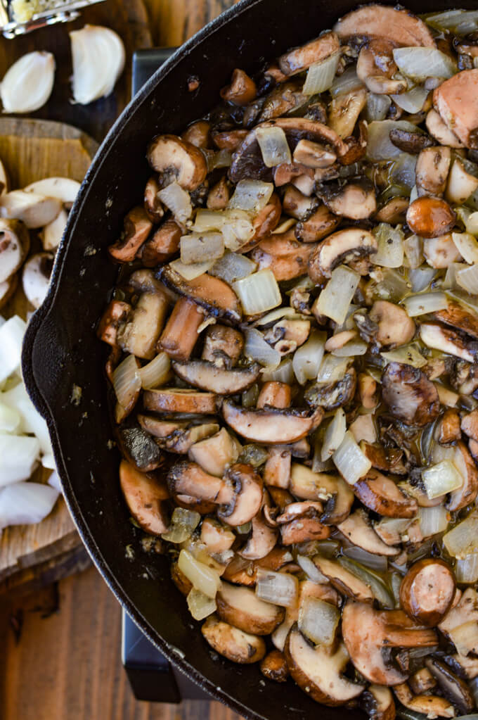 A cast iron skillet with sauteéd mushrooms and onions. A wooden board with raw chopped onions and raw mushrooms next to the pan.