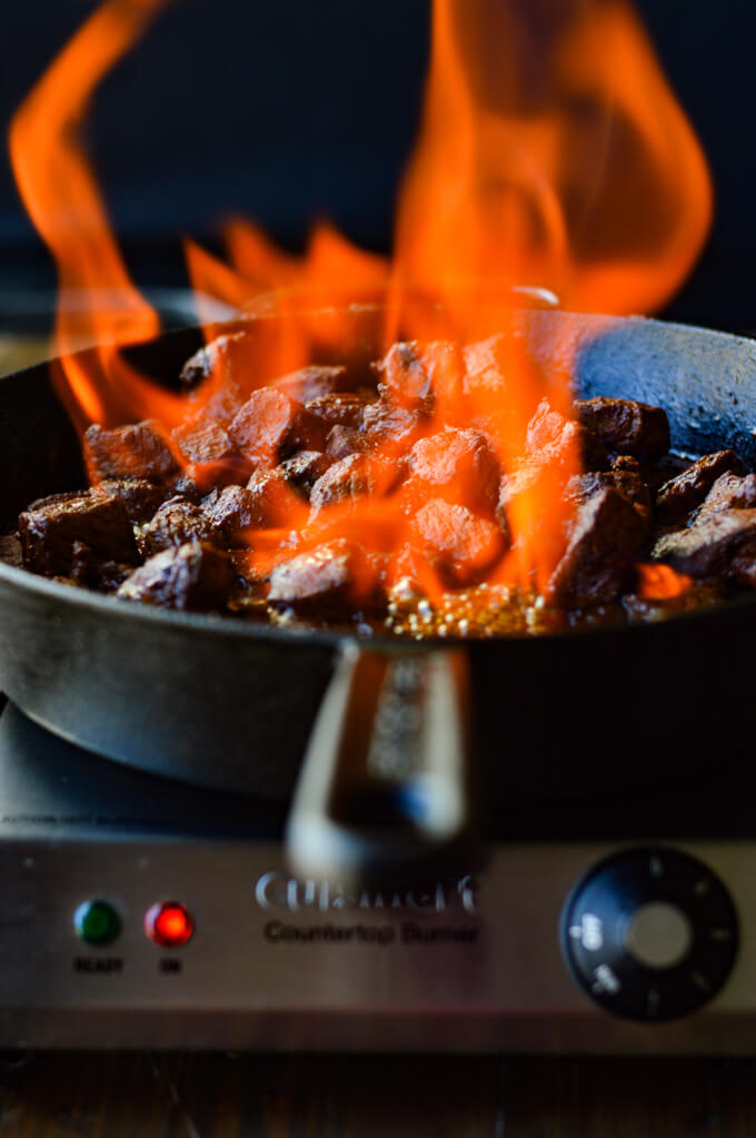A front view of a cast iron skillet with flambé beef stroganoff while the fire is flaring.