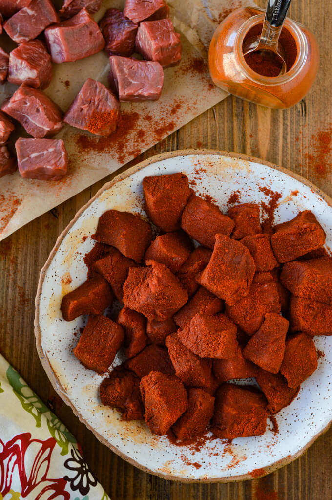 Chunks of raw sirloin steak coated with smoked paprika. Other uncoated steak sits next to it on butcher paper with a jar of smoked paprika.