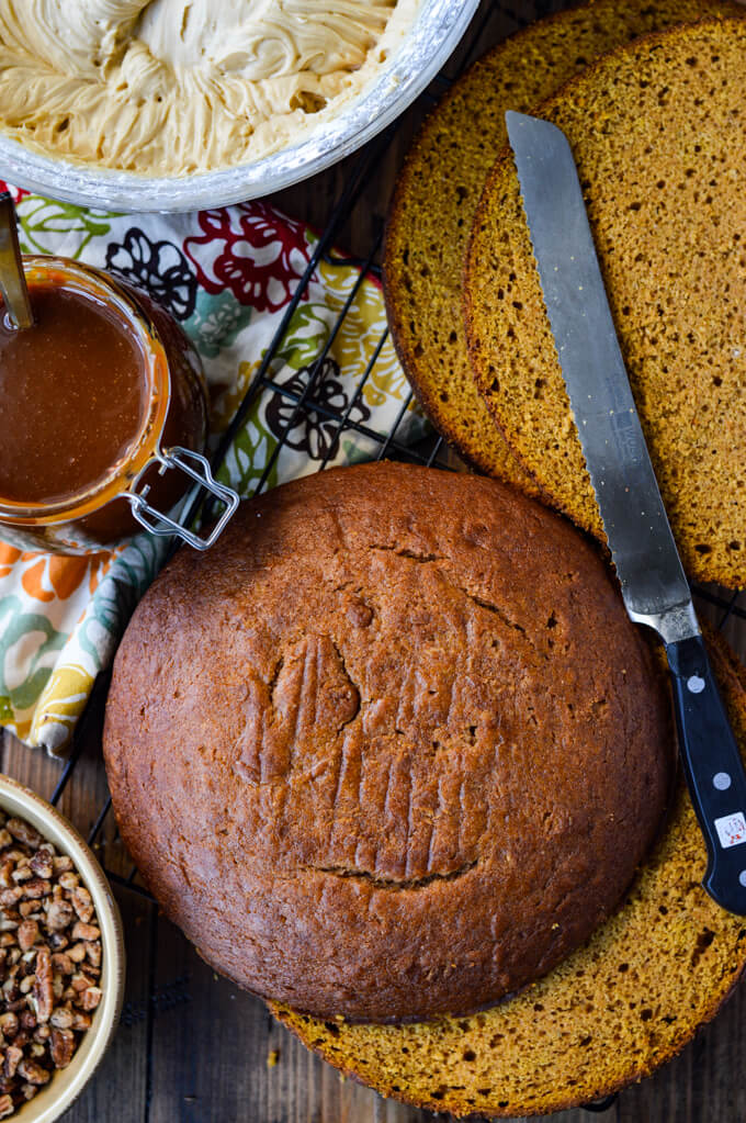 Two round pumpkin cakes are sliced horizontally for layering. A serrated knife lays on top of them. A bowl of icing, caramel syrup and pecans sit next to the cakes. A colorful napkin is in the photo as well.