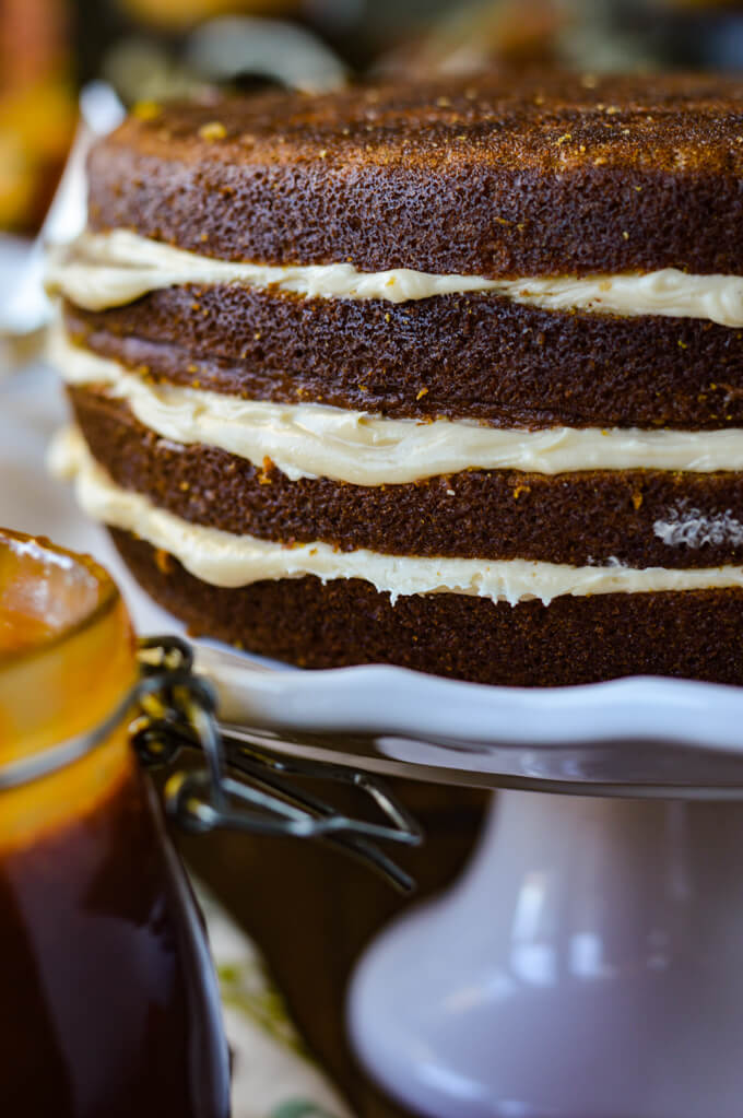 A close up view of frosting between the layers of a pumpkin cake. The cake sits on a white cake stand and there's a jar of caramel sauce next to it.