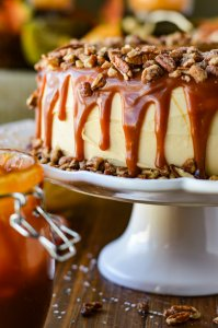 A frosted layered pumpkin cake with caramel dripping down its sides and coated on top with a layer of pecans. The cake sits on a white cake platter with a jar of caramel sauce beside it.