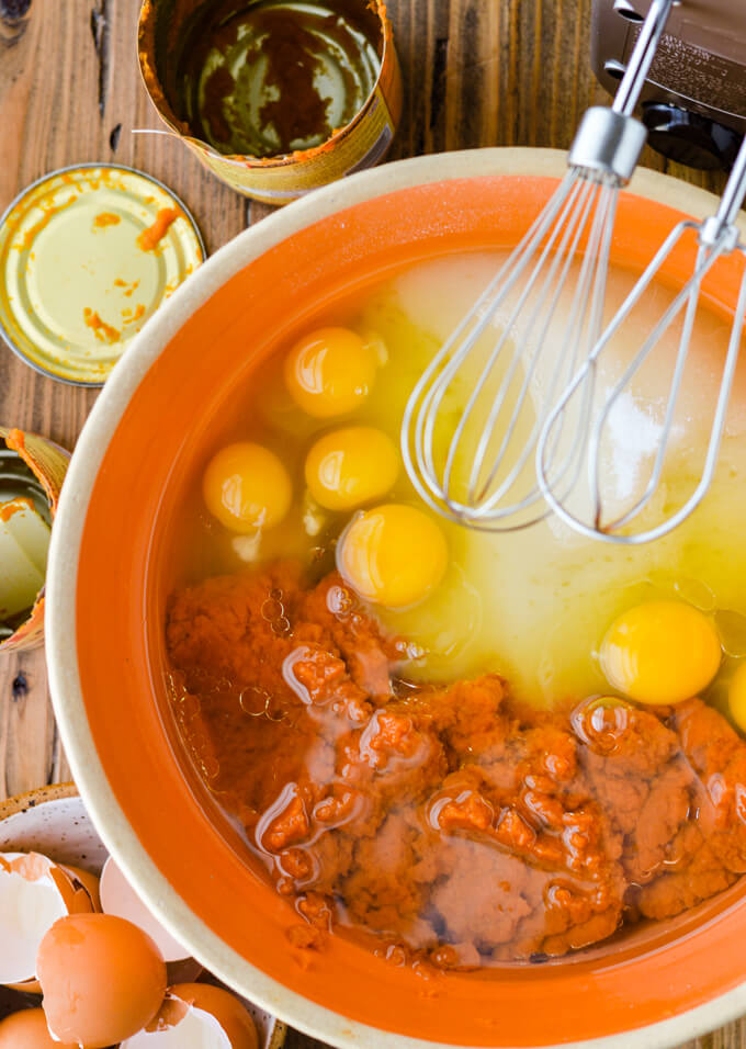 An orange mixing bowl with canned pumpkin, sugar and eggs in it. Hand mixer beaters sit above it. An empty can of pumpkin and lots of egg shells sit next to the bowl.
