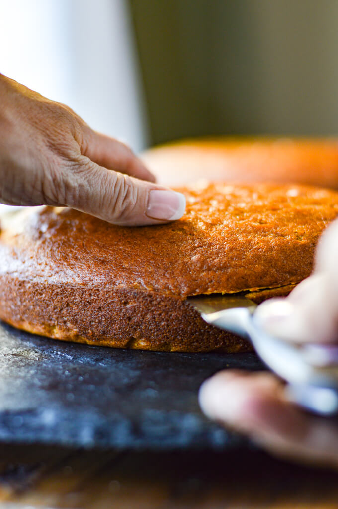 A round pumpkin cake being cut horizontally with a serrated knife on a black lazy susan.