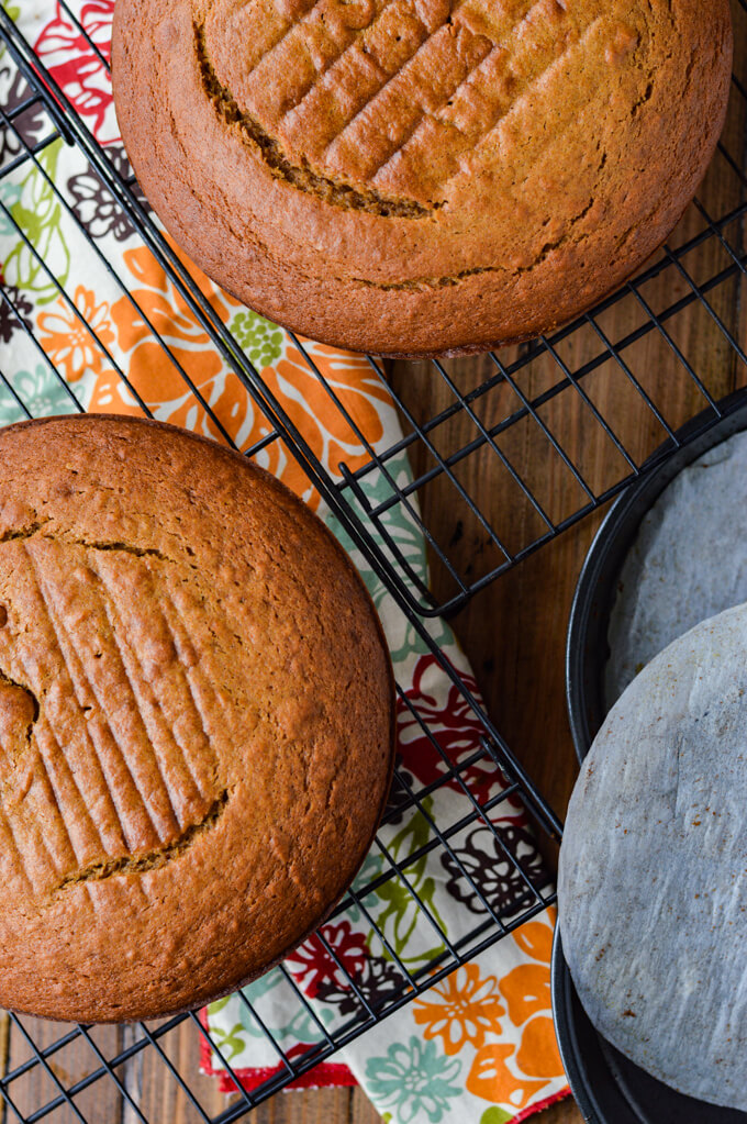 Two round pumpkin cakes are cooling on baking racks with a colorful napkin underneath them. An empty round cake pan with parchment paper sits next to the racks.
