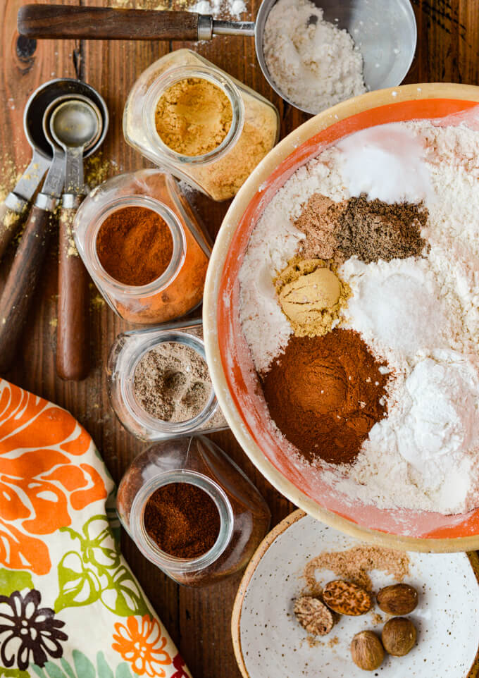 An orange mixing bowl with flour and spices dumped on top. Jars of spices, measuring spoons and a colorful napkin sits next to it.