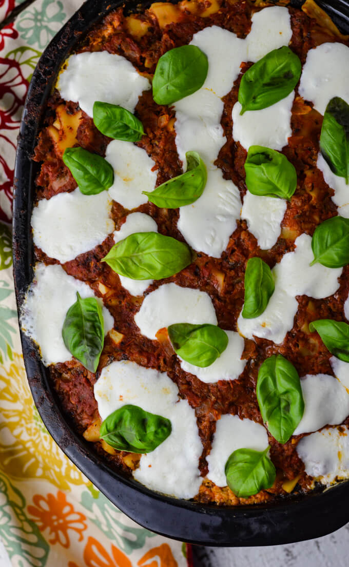 A cooked crockpot lasagna with dollops of fresh mozzarella cheese and fresh basil leaves. A colorful napkin sits beside the crockpot.