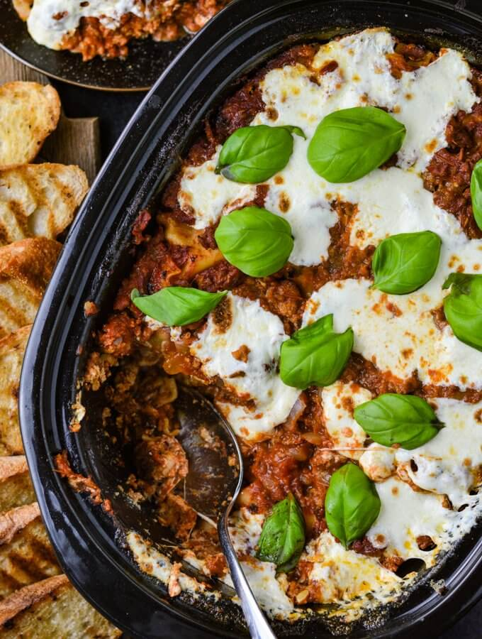 A cooked crockpot lasagna with dollops of fresh mozzarella cheese and fresh basil leaves. A spoonful has been removed from the pan.