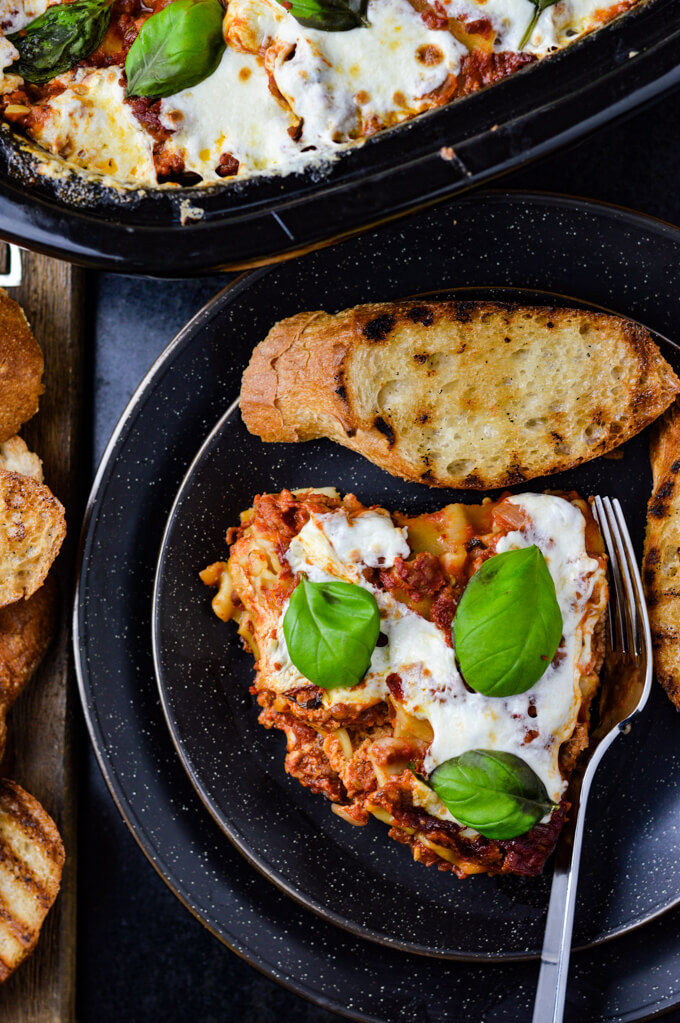 A slice of homemade lasagna with fresh mozzarella and basil leaves on top sits on a black pate with toasted slices of toasted garlic bread. The pan of lasagna sits in the corner of photo.