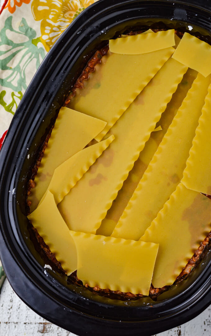 A crockpot holds layers of lasagna with a shot of dry noodles broken to fit in the pan.