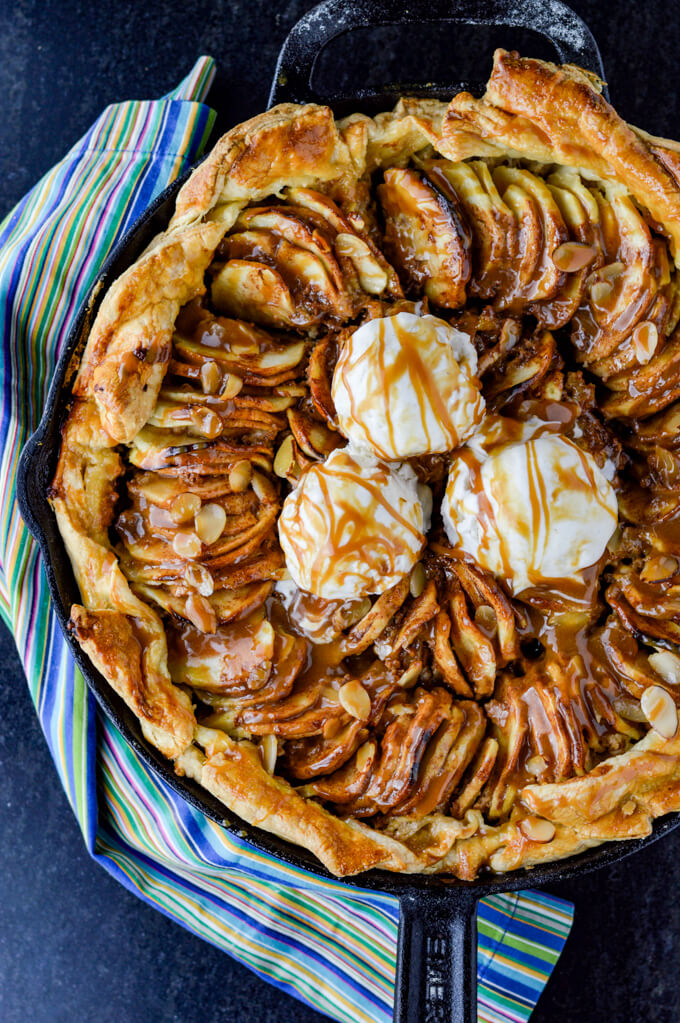 A Caramel Apple Galette with a puff pastry crust in a cast iron pan. A blue striped napkin sits next to it.