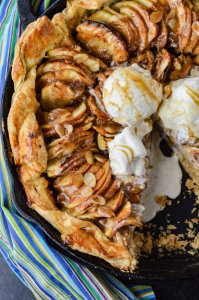 A close-upshot of a Caramel Apple Galette with a puff pastry crust in a cast iron pan. A blue striped napkin sits next to it. Three scoops of ice cream sit on the apples. A slice is taken out of it and the ice cream is melting into the pan.
