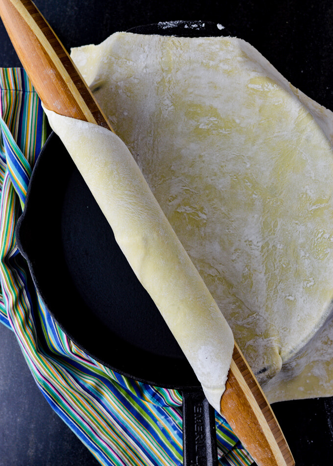 A rolling pin is rolling out a sheet of puff pastry onto a large black cast iron skillet. A blue striped napkin sits beside the skillet.