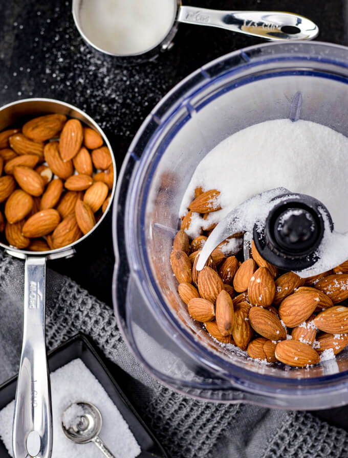 A food processor with whole almonds, sugar and salt. Measuring cups of almonds and sugar and a black small saucer of coarse salt sits next to the processor.
