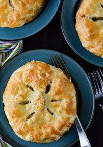 A chicken pot pie on a blue place wit two other pies in the corner of the photo. Forks and a blue striped napkin sits next to the main pot pie.