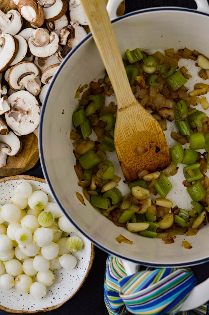 A white Dutch oven holds sauteed onions, celery and garlic. A small bowl of frozen petite onions and a wooden butting board with sliced mushrooms sit next to the Dutch oven.