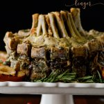 Herbed Crown Roast of Pork sitting on a white platter with rosemary garnish.