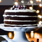 A layered gingerbread cake with eggnog icing and sugared cranberries sits on a white cake stand. A folded white napkin sits next to it with a cake server on it. Christmas lights are blurred in the background.