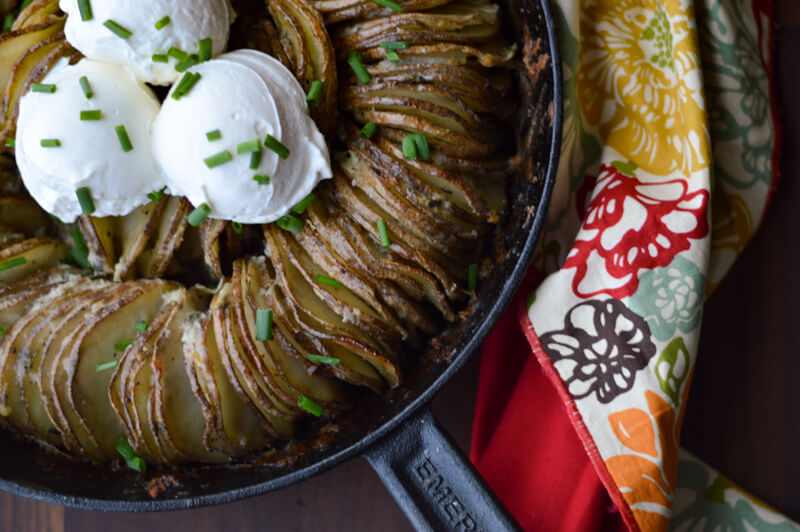 Hasselback Buttery Potato Ring in a cast iron skillet with a colorful napkin beside it.