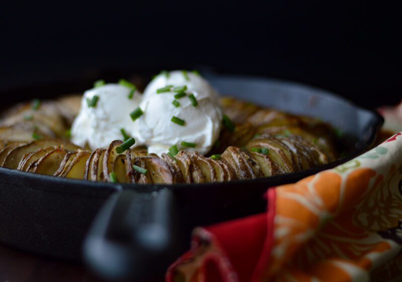 A front view of a Hasselback Buttery Potato Ring in a cast iron skillet with a colorful napkin beside it.